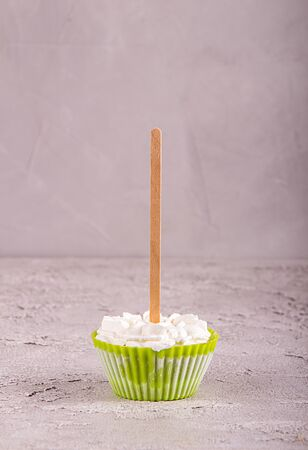 Row of ice cream lollies with whipped cream frozen in muffin molds on gray background. Imagens