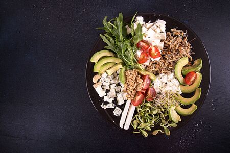 Healthy vegetarian salad of avocado, cherry tomato, sprouts, arugula, feta; blue cheese, cereals. Healthy eating food. Copy space. Top view