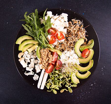 Healthy vegetarian salad of avocado, cherry tomato, sprouts, arugula, feta; blue cheese, cereals. Healthy eating food. Imagens