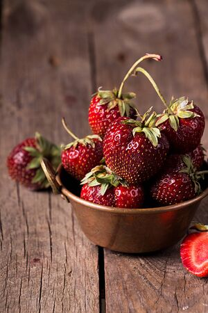 Fresh ripe strawberries in cooper bowl on rustic wooden background