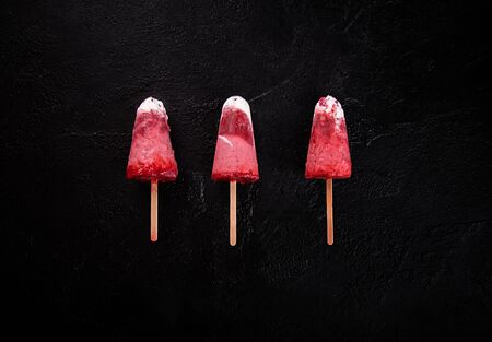 Strawberry ice cream  lolly pops with whipped cream on gray background. Top view