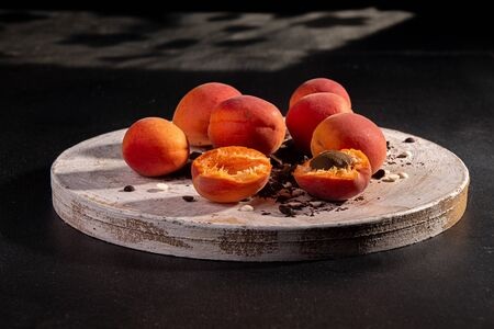 Natural organic apricots on white wooden over on dark background. Imagens