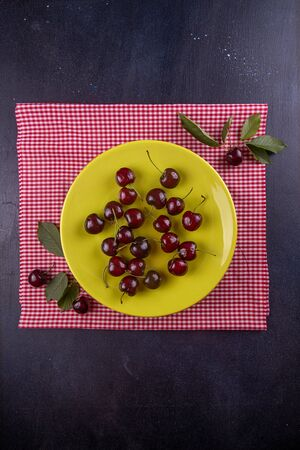 Sweet cherries on olive color plate over on white checkered fabric on dark background