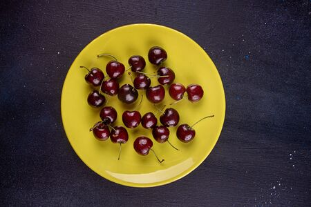 Sweet cherries fruits on olive color plate over on dark blue background Imagens