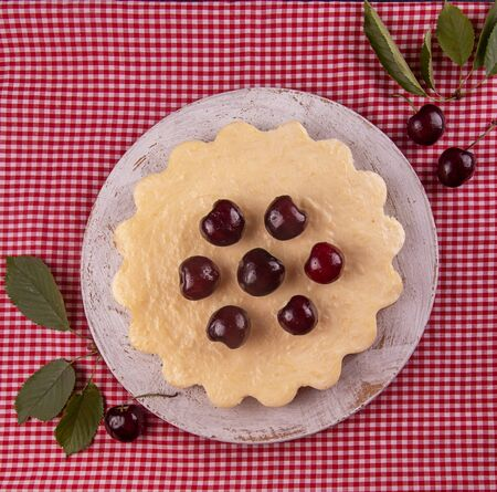 Homemade cheesecake decorated with sweet cherries over on white red checkered fabric background. Top view