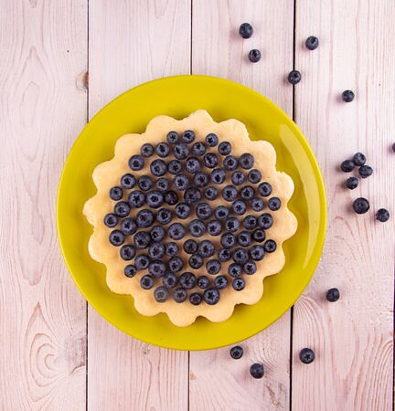 Homemade cheesecake decorated with blueberry over on white wooden background. Top view