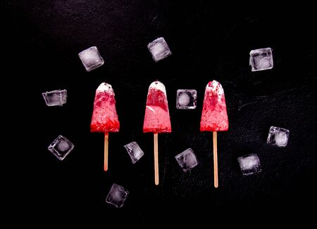 Strawberry ice cream pops with whipped cream on black background decorated with ice cubes. Top view. Flat lay