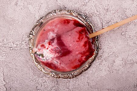 Melted strawberry ice cream  pops with whipped cream over on silver plate on gray background. Top view Imagens