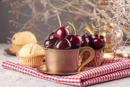 Sweet cherries in cooper cups and muffins