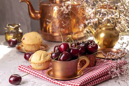 Sweet cherries in cooper cups and muffins against of background with old cooper teapot. Summer dessert.
