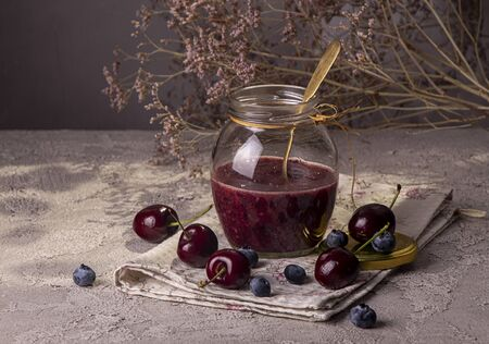 Smoothie jam of sweet cherry and bluberry in glass jar