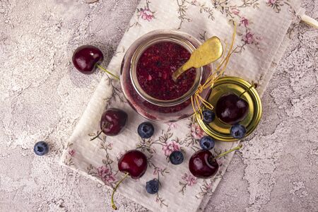 Smoothie jam of sweet cherry and bluberry in glass jar. Top view