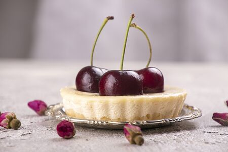 Small portion cheesecake with fresh sweet cherries against of gray background Imagens
