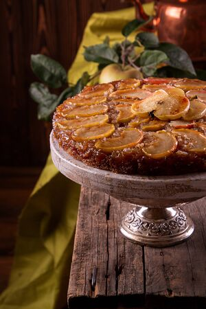 French sweet pie tart tatin apple cake upside down and fresh apples over on old rustic wooden background.