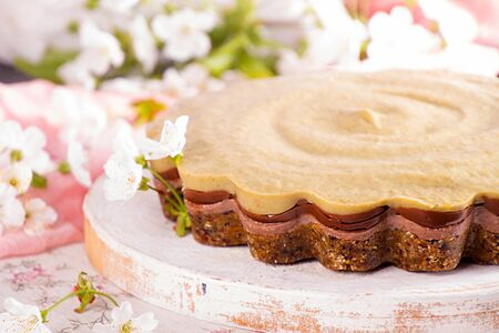 Vegan raw food healthy eating cake without baking. From ingredients nuts, dates, prunes, avocado, banana, cocoa, chocolate, without baking, gluten free. White background, blooming apple tree flowers