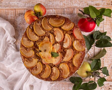 French sweet pie tart tatin apple cake upside down and fresh red apple over on old rustic wooden background. Top view