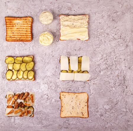 Step-by-step preparation sandwich with chicken meat, marinated cucumbers, mozzarella cheese and sauces over on grey concrete background. Geometric Layout Ingredients composition. Top view. Flat lay