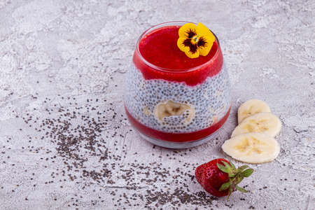 Chia seeds with fresh banana and strawberry in glass. Copy space