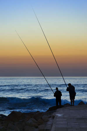 Fishermans at sunset, Caesarea harbor, Israel Stock Photo