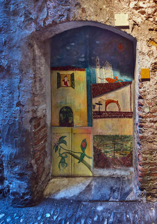 Painted door in Albenga  Albenga is an ancient city, founded in pre-Roman period, situated on the Gulf of Genoa on the Italian Riviera in the Province of Savona in Liguria, Italy   Stock Photo