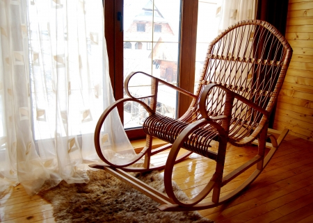 cosiness: Wooden rocking-chair at a window Stock Photo