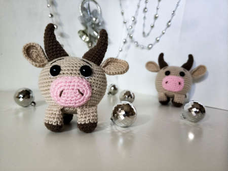 Pair of bulls on white background with Christmas decorations. Crocheted soft toys, handmade. 2021