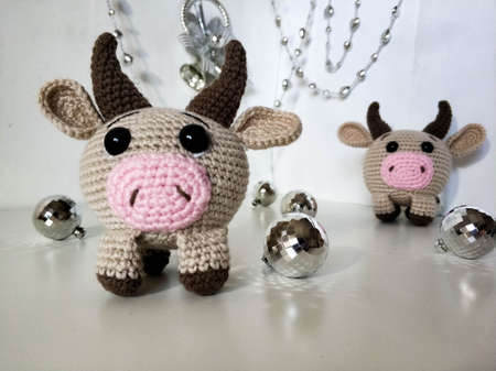 Beige knitted toy decoration of bull cow in the foreground. For new year, christmas 2021.on a white background with a Christmas tree and santa claus.