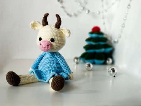 Crochet soft toy cow bull of beige color in a blue dress on white background. Symbol of the new year 2021. Celebratory decorations, tree.