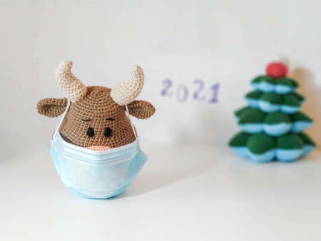 Crochet soft toy bull cow in blue medical protective mask. On a light background with a toy fir tree, blurry inscription 2021. New Year Christmas 2021