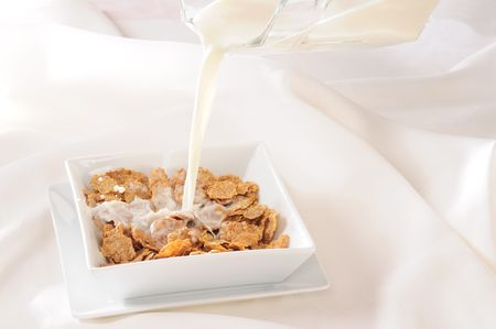 Pouring milk into a bowl. photo