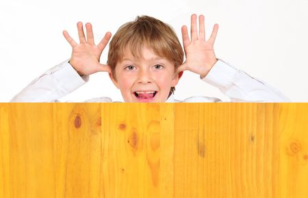 Cheeky boy behind board. Stock Photo - 5670744