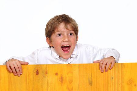 Surprised boy behind board. photo