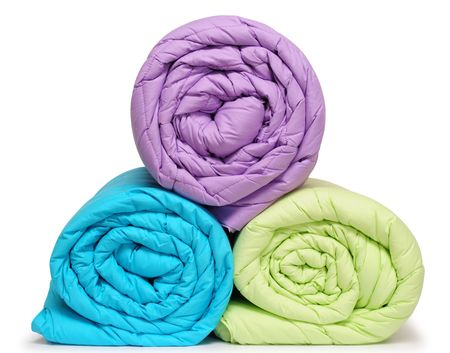 Colorful duvet rolls. Isolated.