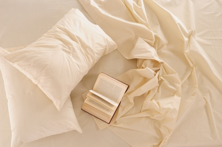 bed sheet: Book on messy bed.