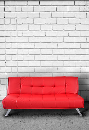 sully: Red sofa against brick wall Stock Photo