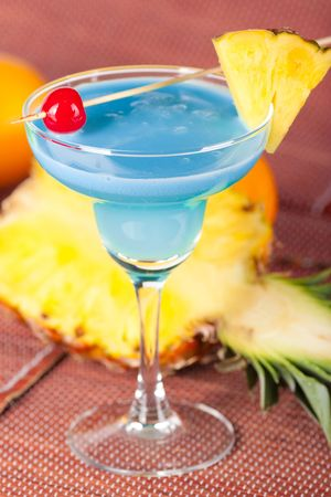 Blue alcohol cocktail with pineapple, orange and cherry Stock Photo - 5809410