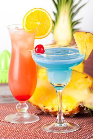 Two tropical cocktails with pineapple, orange and cherry
