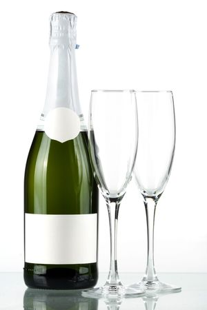 Bottle of champagne with blank label and with two empty glasses photo