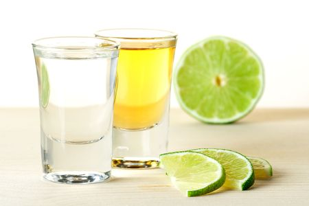 Blanc and Gold Tequila with lime slices on wood table isolated on white background photo