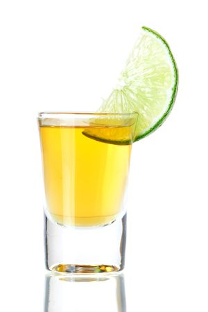 Gold Tequila with lime slice isolated on white background