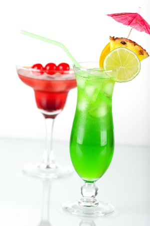 Green and red tropical cocktails with pineapple and cherry photo