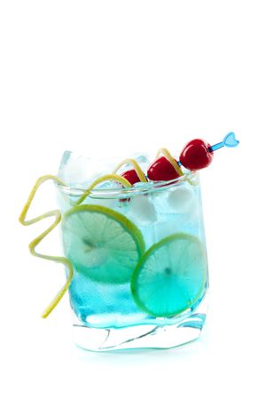 Blue alcohol cocktail with lemon and maraschino slices isolated on white background photo