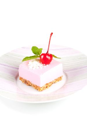 maraschino: Pink cheesecake with maraschino cherry and mint on plate