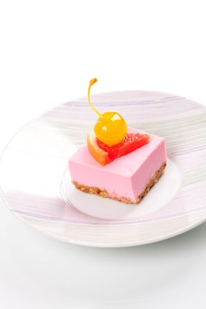maraschino: Pink cheesecake with maraschino cherry and grapefruit slice on plate