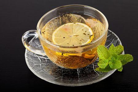 english breakfast tea: Cup of green tea with lemon and mint on dark wood table