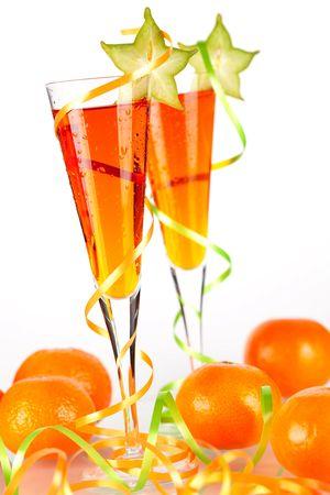 Two orange alcohol cocktails with carambola and mandarines isolated on white background photo