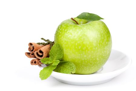 A Ripe Green Apple with mint and cinnamon on plate isolated on white background photo