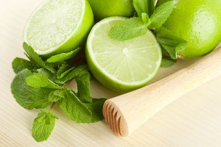 Mojito mix on wood table: lime, mint and muddler photo