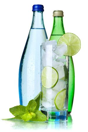 green glass bottle: Glass of water with lime and ice, two bottles with mineral water. Isolated on white background. Stock Photo