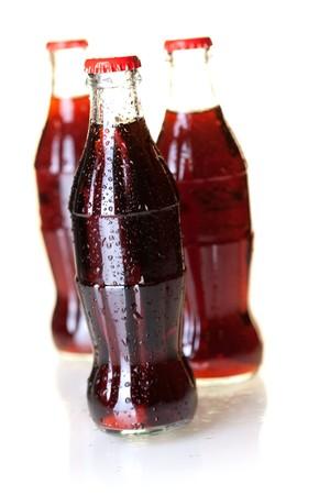Gotas de tres botellas de cola fría con agua. DOF pequeño, aislado en blanco